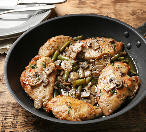 Grilled chicken breast with mushrooms in the black pan