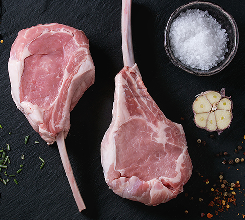 Fresh veal chops with garlic and salt on black board
