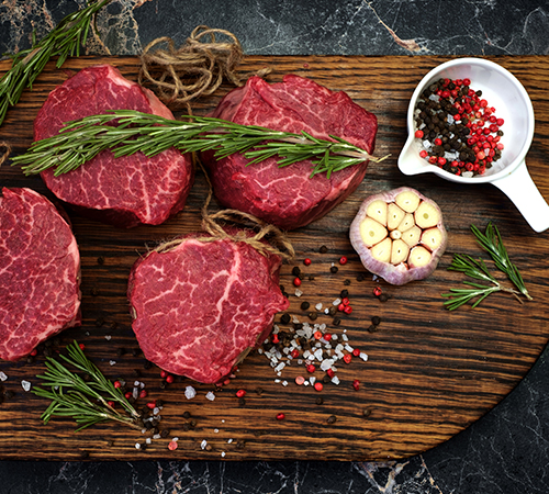 Filet mignon steaks spiced with rosemary and garlic on wooden board