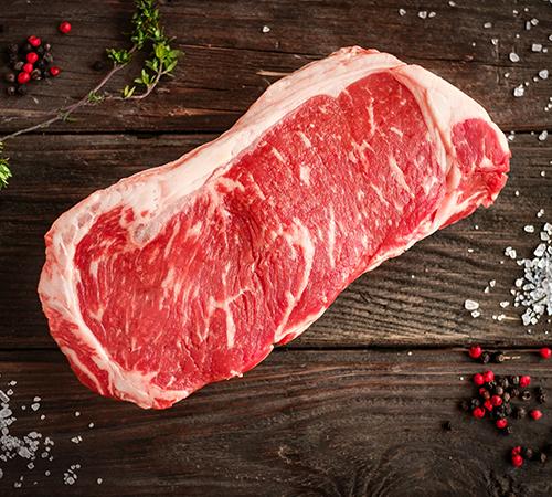 Grass fed boneless strip steak on wood
