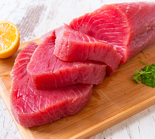 Fresh tuna sliced on wooden board